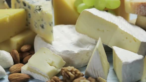Assorted Different Types of Cheeses with Fruits, Nuts, Dried Fruits
