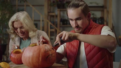 Young Man Carves a Lamp for Halloween