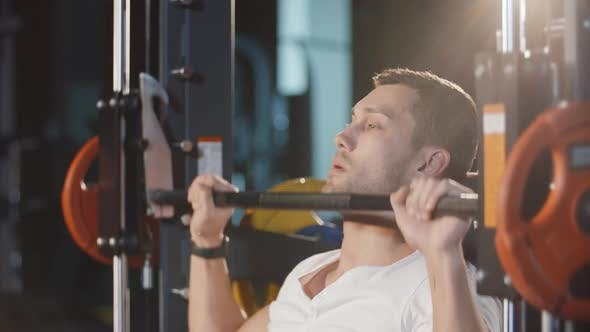 Cover Image for Muscular Man Doing Workout Exercise With Barbell Machine Training Hands Back and Shoulders in Gym