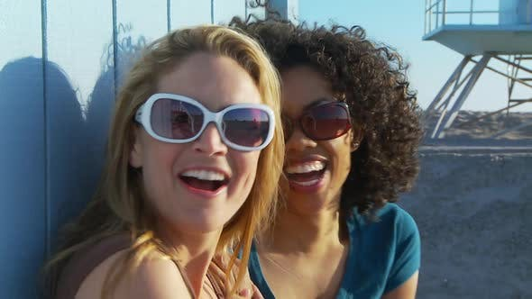 Two women friends in sunglasses at the beach