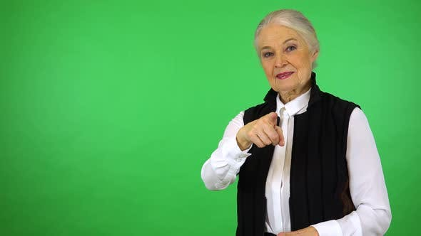 Thumbnail for An elderly woman points at the camera and smiles - green screen studio