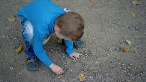 Little Boy legt ein Bild von Steinen