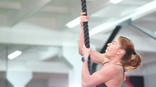 Woman Trains on a Rope in the Gym