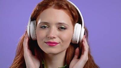 Cute Woman with Wireless Headphones on Purple Studio Background