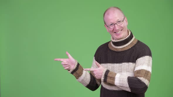 Thumbnail for Happy Mature Bald Man with Turtleneck Sweater Showing Something