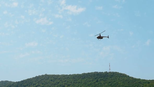 Cover Image for Black Helicopter Hovers And Flies In Air Against Blue Ssky With Mountains In Background