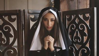 Nun Pray And Looks Into Camera