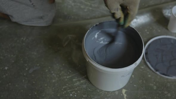 Thumbnail for Erector Carefully Stirs Gray Paint In Plastic Pail To Apply It On Walls.