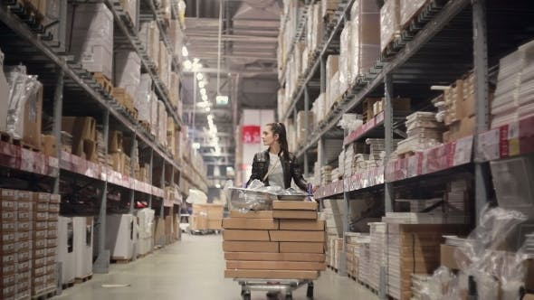 Thumbnail for A Young Brunette Woman Pushing a Trolley With Lots Of Boxes Between Shelves With Goods In a