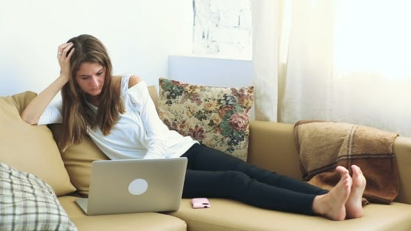 Thumbnail for Young Woman Using Laptop On The Sofa