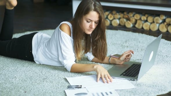 Thumbnail for Young Brunette Lying On The Carpet And Using Laptop