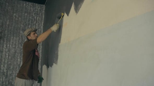Thumbnail for Man Is Actively Using a Fur Roller When Painting Walls Gray Paint.