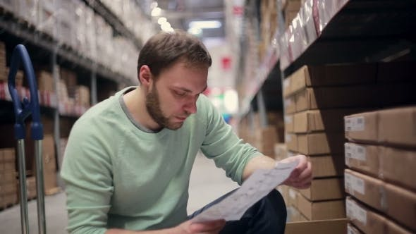 Thumbnail for A Man With a Beard In a Blue Sweater Checking His List In a Warehouse