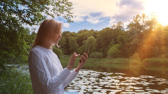 Cover Image for Beautiful Girl Using SmartPhone Sitting Near Lake in City Park 1