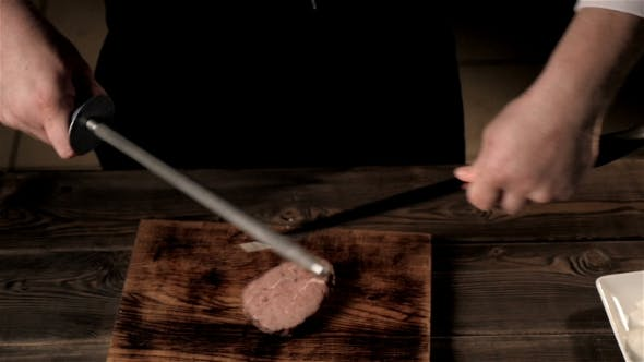 Thumbnail for Midsection Of Male Chef Sharpening Knife In Commercial Kitchen