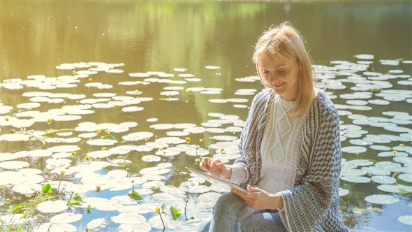 Cover Image for Beautiful Girl Using Tablet PC Sitting Near Lake in City Park 2 on Sunset