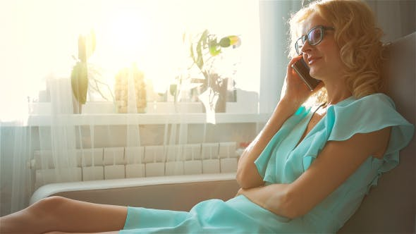 Thumbnail for Happy Beautiful Girl Sitting on Sofa at Home and Talking on the Phone 2