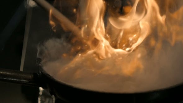 Thumbnail for Chef Cooking With Fire In Frying Pan.Professional Chef In a Commercial Kitchen Cooking Flambe Style
