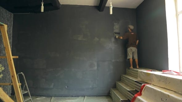 Thumbnail for Man Paints Wall For Photo Studio In a Grey Background With a Roller, Standing On Stairs, Near Window