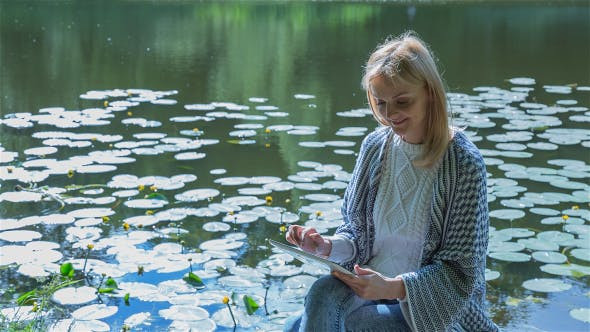 Thumbnail for Beautiful Girl Using Tablet PC Sitting Near Lake in City Park 2