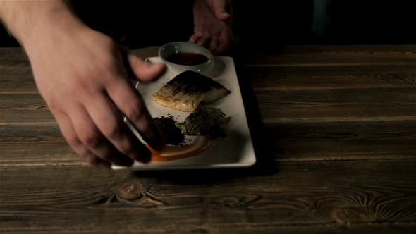 Thumbnail for Healthy Food Concept: Chief Serving Hot Baked Fish Piece Over White Plate On Wooden Table