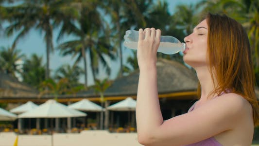Girl Drinks Cold Water at Sunny Beach