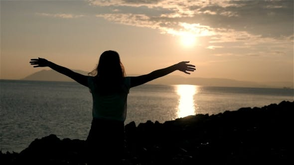 Thumbnail for Silhouette Of Wonderful Young Woman Watching To Sea And Raising Her Hands