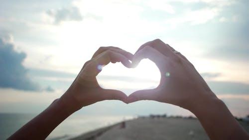 Mains montrer coeur au coucher du soleil, amour
