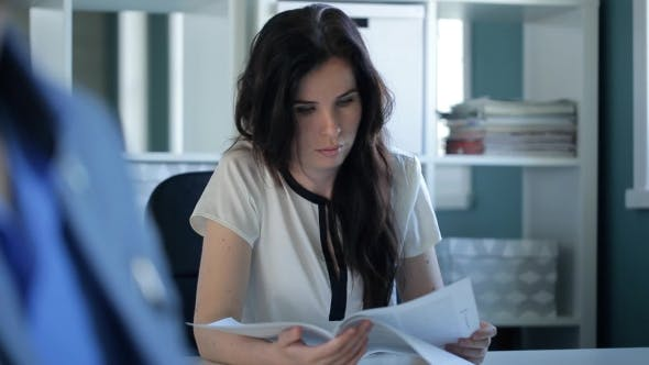 Thumbnail for Young Beautiful Female Is Reading Document Sitting In Office.