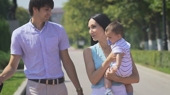 Thumbnail for Young Family Walking On The City Park With a Little Boy In Her Arms.