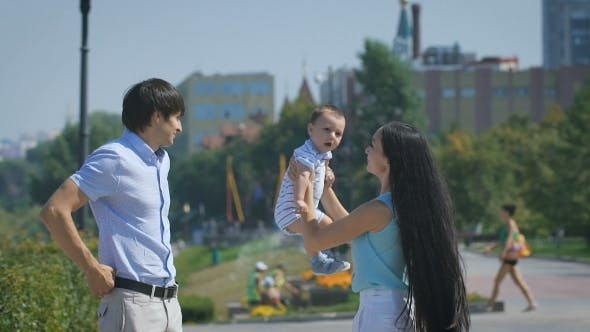 Thumbnail for Happy Family. Young Mother Throws Up Baby In The Sky, On Sunny Day.