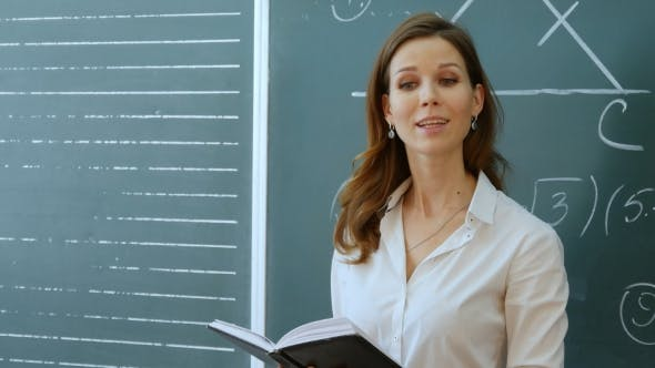Thumbnail for Teacher With Book Dictates In Classroom At School.