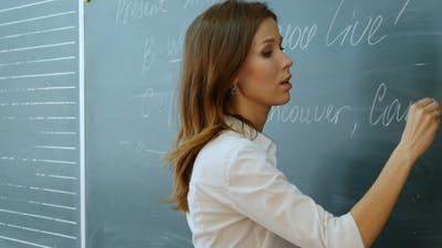 Teacher Writing On The Blackboard .