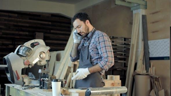 Thumbnail for Zimmermann Arbeiten an seinem Handwerk in einer staubigen Werkstatt und sprechen Telefon.
