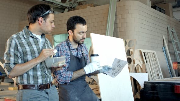 Thumbnail for Two Carpenters Discussing Work And One Of Them Eating.