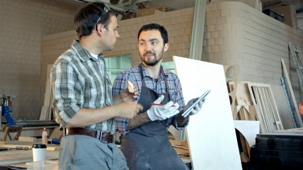 Thumbnail for Two Carpenters Discussing Ideas One Of Them Eating And Another Is Writing In Notebook At Workshop.