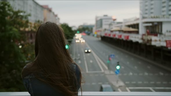 Thumbnail for Beautiful Girl Standing On The Bridge, Looks At The City, Wind Blows Her Hair. Back View,