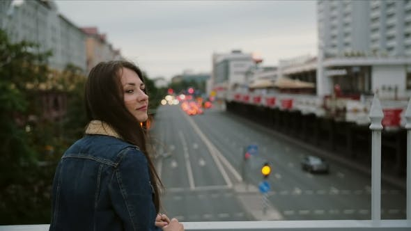 Thumbnail for Beautiful Girl Standing On Bridge, Looks At The City, Then Turns To The Camera And Smiling. Wind