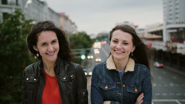 Thumbnail for Two Beautiful Girls Standing On The Bridge, Smiling, Laughing And Looks At The Camera. Wind Blows