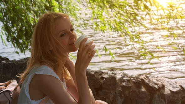 Thumbnail for Beautiful Girl Sitting Near Lake in City Park and Drinking Coffee 2