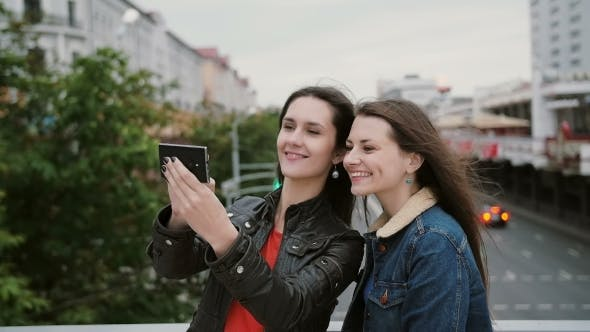 Thumbnail for Two Girls Best Friends Taking Selfie, Standing On The City Bridge, Talking, Smiling, Laughing. .