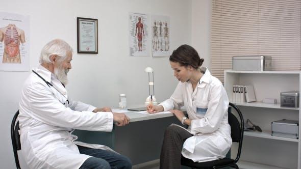 Der alte Doktor spricht mit der jungen Ärztin.