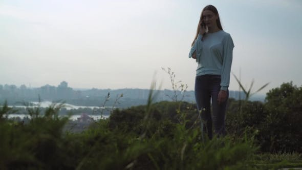 Thumbnail for Beautiful Young Girl Standing On The Hill And Talking On The Phone.