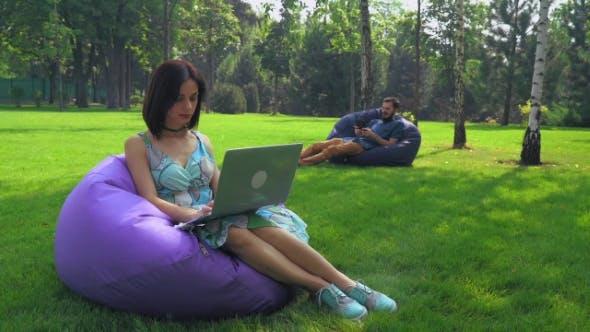 Thumbnail for Das Mädchen Brünette sitzt in einem Stuhl im Park und Arbeiten auf einem Laptop.