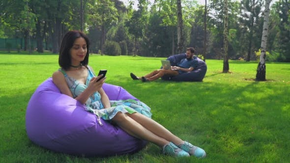 Thumbnail for Young Attractive Brunette Girl Is Sitting In a Chair In The Park And Gaining a Message On The Phone.