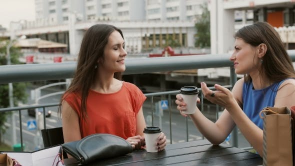 Thumbnail for Attractive Women Friends Communicate In a Cafe With a View Of The Traffic, Talking, Drinking Coffee