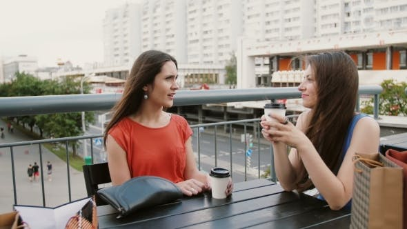 Thumbnail for Beautiful Women Drinking Coffee Communicate In a Cafe With a View Of The Traffic