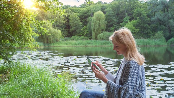Thumbnail for Beautiful Girl Using Tablet PC Sitting Near Lake in City Park 3