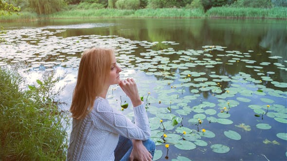 Thumbnail for Beautiful Girl Sitting Near Lake in City Park and Dreaming 2