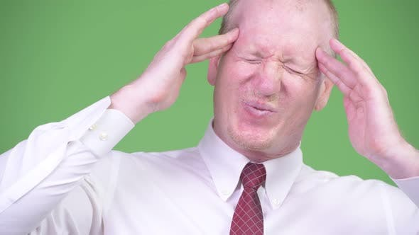 Cover Image for Stressed Mature Bald Businessman Having Headache
